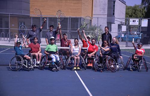 Smiling jr wheelchair tennis players pose for a group photo