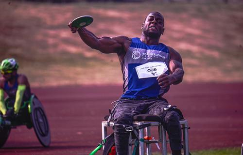 A young muscular man sits in a throwing frame and prepares to release a discus from his hand.