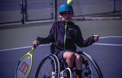 A young wheelchair tennis player prepares to hit an approaching tennis ball.