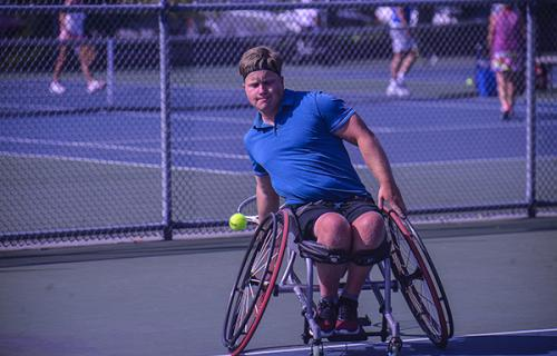 A young white male wheelchair tennis player wearing a royal blue shirt and black shorts prepares to hit a tennis ball that's approaching him on an outdoor tennis court.